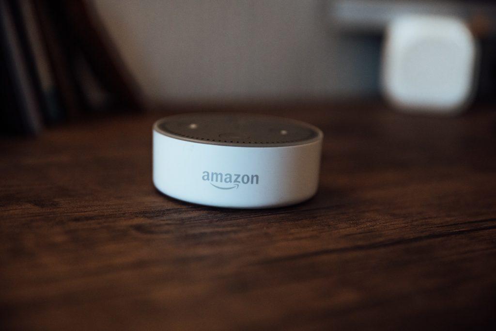 An Amazon smart speaker on a wooden coffee table